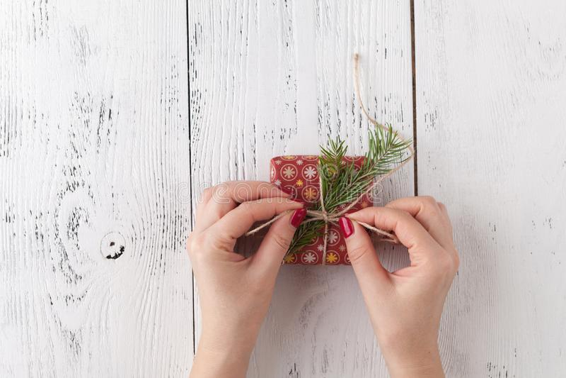 Δημιουργικό χόμπι Τα χέρια γυναικών ` s τυλίγουν το χειροποίητο παρόν διακοπών Χριστουγέννων στο έγγραφο τεχνών με την κορδέλλα σ στοκ φωτογραφία με δικαίωμα ελεύθερης χρήσης