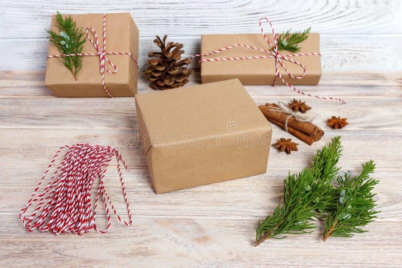 Δημιουργικό χόμπι Τύλιγμα δώρων Συσκευασία των σύγχρονων κιβωτίων χριστουγεννιάτικου δώρου στο μοντέρνο γκρίζο έγγραφο με την κόκ στοκ εικόνα με δικαίωμα ελεύθερης χρήσης