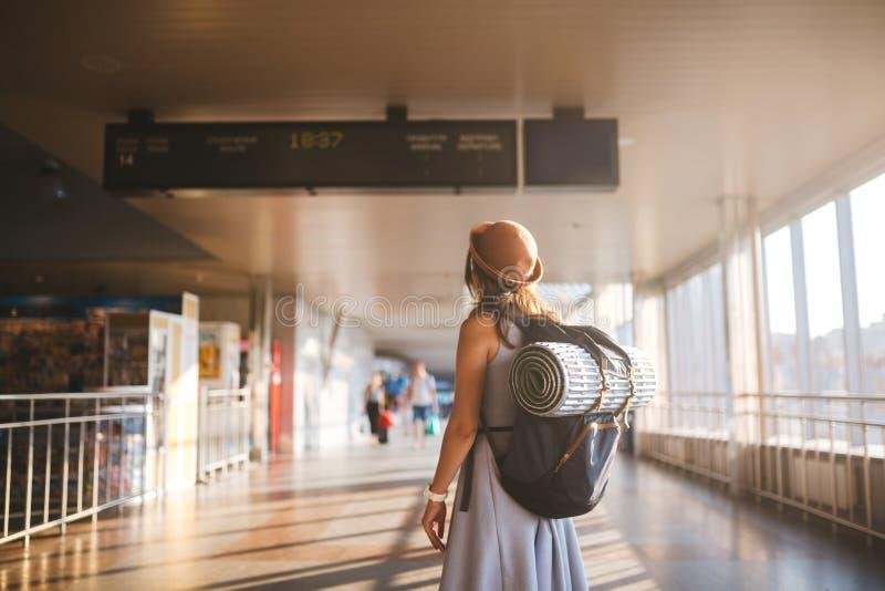 Δημόσιες συγκοινωνίες ταξιδιού θέματος νέα γυναίκα που στέκονται με πίσω στο φόρεμα και το καπέλο πίσω από το σακίδιο πλάτης και  στοκ φωτογραφία με δικαίωμα ελεύθερης χρήσης