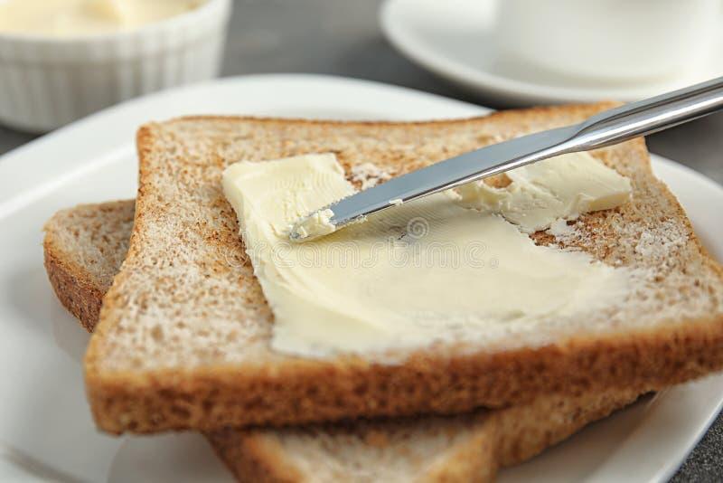 Διάδοση του νόστιμου βουτύρου επάνω στη φέτα του ψωμιού με το μαχαίρι στο πιάτο στοκ εικόνα