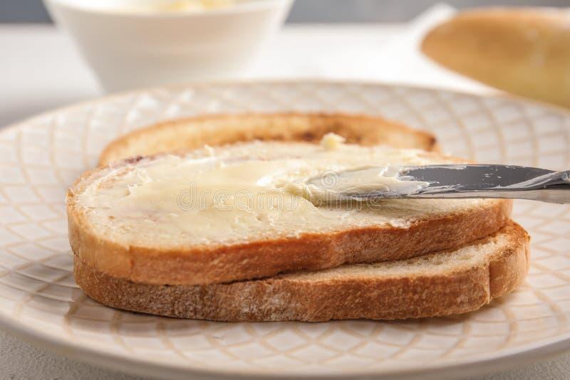 Διάδοση του νόστιμου βουτύρου επάνω στη φέτα του ψωμιού με το μαχαίρι στο πιάτο στοκ εικόνες