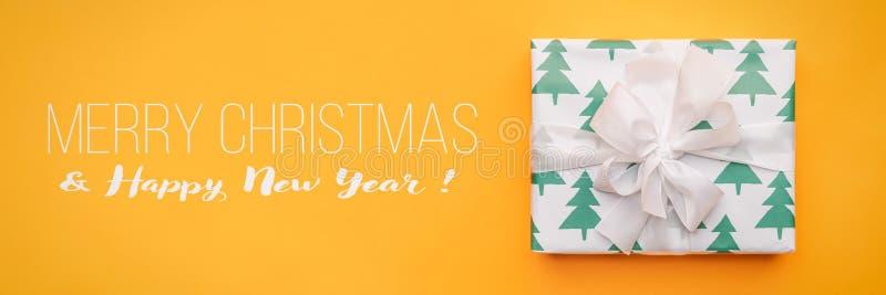 διάνυσμα απεικόνισης Χριστουγέννων eps10 εμβλημάτων Όμορφο δώρο Χριστουγέννων που απομονώνεται στο φωτεινό κίτρινο υπόβαθρο Το τυ στοκ φωτογραφία με δικαίωμα ελεύθερης χρήσης
