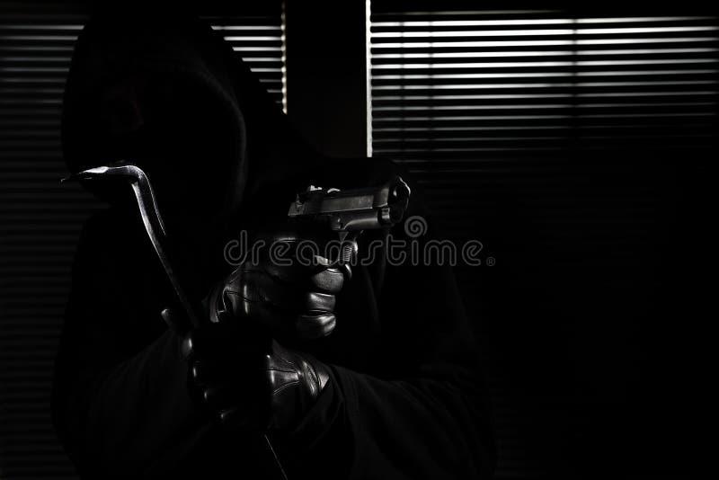 Διάρρηξη και ληστεία ο επιδέξιος επαγγελματικός καλυμμένος διαρρήκτης που κρατά ένα πυροβόλο όπλο και έναν λοστό και που σπάζει σ στοκ φωτογραφία με δικαίωμα ελεύθερης χρήσης