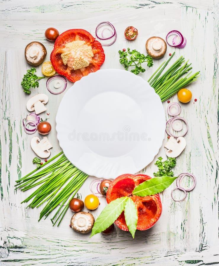 Διάφορα λαχανικά και μαγειρεύοντας συστατικά καρυκευμάτων γύρω από το κενό πιάτο στο ελαφρύ αγροτικό ξύλινο υπόβαθρο, τοπ σύνθεση στοκ φωτογραφία με δικαίωμα ελεύθερης χρήσης