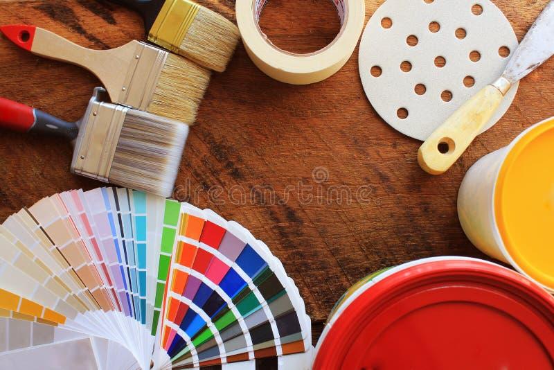 Διάφορα εργαλεία ζωγραφικής, εξαρτήματα και δείγματα χρώματος για την εγχώρια ανακαίνιση στο ξύλινο υπόβαθρο στοκ φωτογραφία