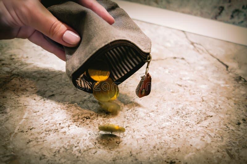 Διάφορα νομίσματα πέφτουν από ένα κενό πορτοφόλι στο χέρι μιας γυναίκας στοκ εικόνες με δικαίωμα ελεύθερης χρήσης