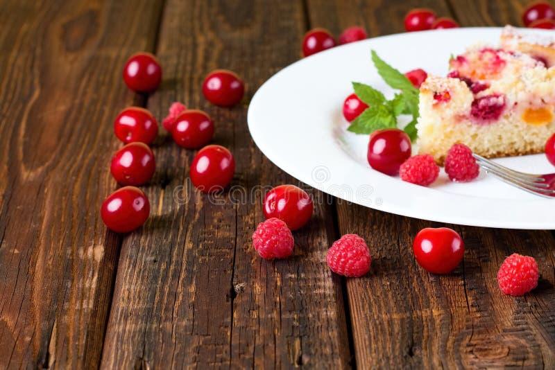 Διάφορα σμέουρα και κεράσια γύρω από το άσπρο πιάτο με το κέικ στοκ φωτογραφίες με δικαίωμα ελεύθερης χρήσης