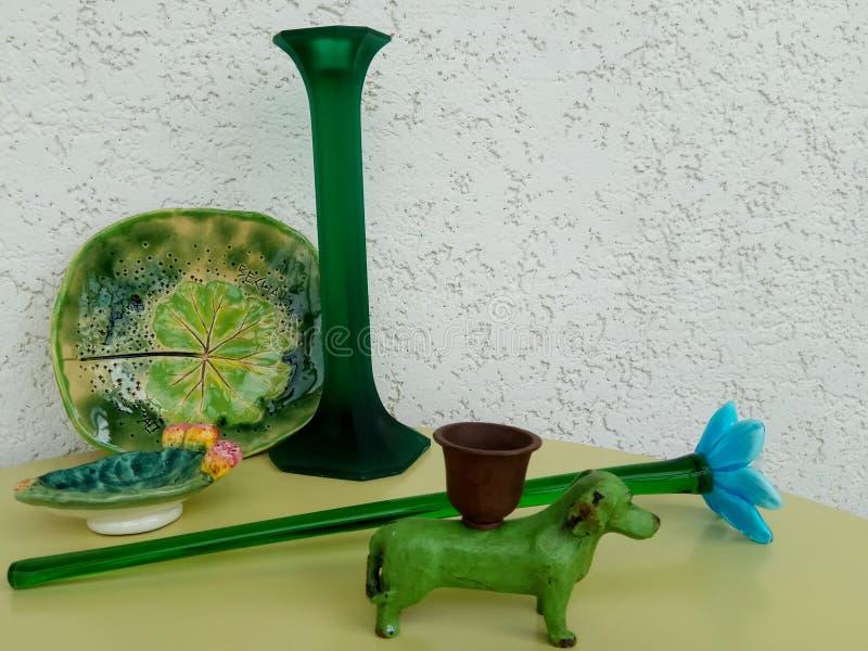 Διάφορα στοιχεία ( κηροπήγιο, σκυλί μετάλλων, λουλούδι γυαλιού και κεραμική που συνδυάζονται σε πράσινο στοκ φωτογραφίες