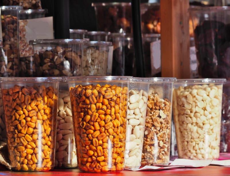 Διάφορα συσκευασμένα πλαστικά εμπορευματοκιβώτια των ξηρών και ψημένων σπόρων, των καρυδιών, του καλαμποκιού και των αμυγδάλων στ στοκ φωτογραφία