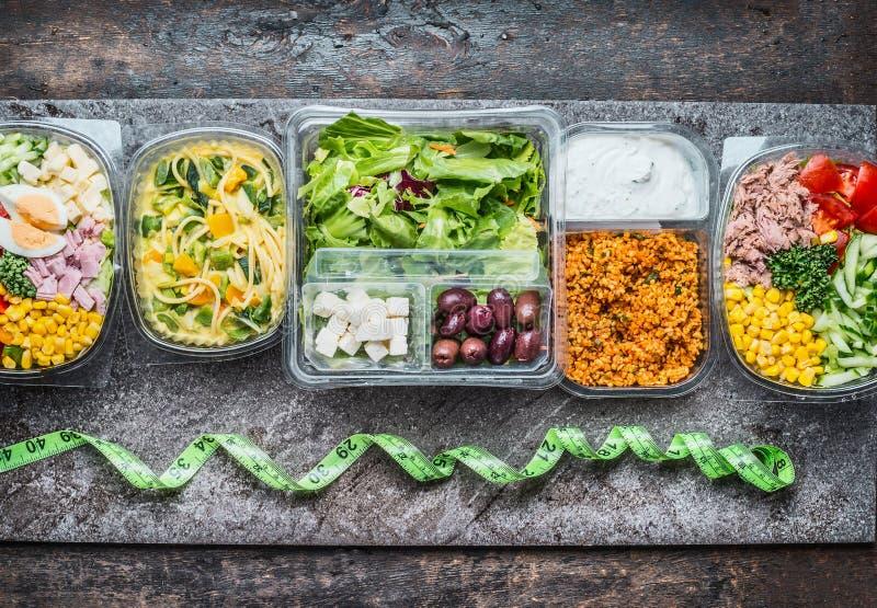 Διάφορα υγιή καλαθάκια με φαγητό στην πλαστική συσκευασία και την πράσινη μετρώντας ταινία στο αγροτικό υπόβαθρο, τοπ άποψη στοκ εικόνες