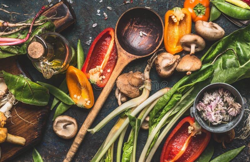 Διάφορα φρέσκα λαχανικά με το ξύλινο μαγειρεύοντας κουτάλι για την υγιείς κατανάλωση και τη διατροφή στο σκοτεινό αγροτικό υπόβαθ στοκ εικόνα