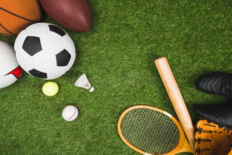 Διάφορες αθλητικές σφαίρες, ρόπαλο του μπέιζμπολ και γάντι, ρακέτα μπάντμιντον στον πράσινο χορτοτάπητα στοκ φωτογραφία με δικαίωμα ελεύθερης χρήσης