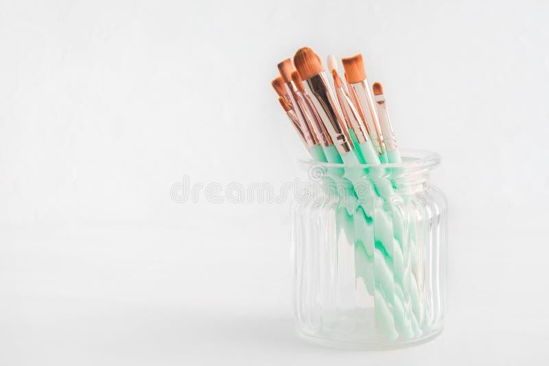 Διάφορες βούρτσες makeup στο βάζο γυαλιού στο ελαφρύ υπόβαθρο με το διάστημα αντιγράφων στοκ φωτογραφία