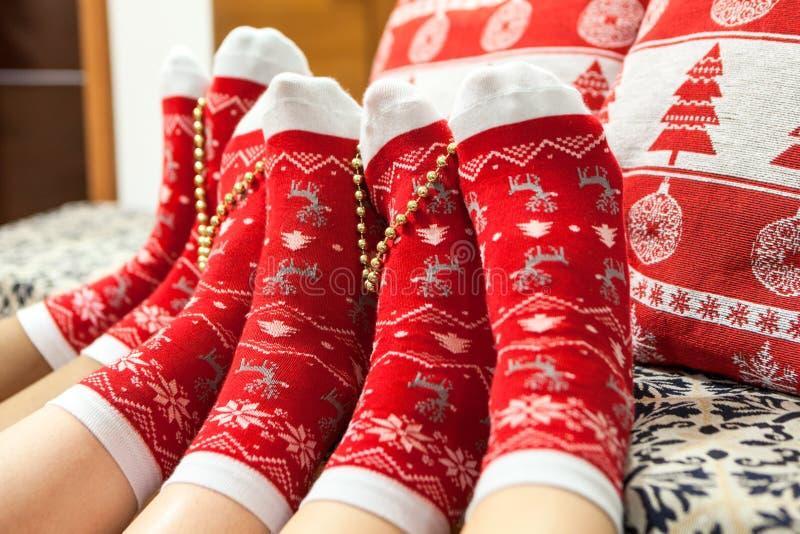 Διάφορες κόκκινες κάλτσες Χριστουγέννων με τα ανθρώπινα πόδια, διακόσμηση Χριστουγέννων στοκ εικόνες