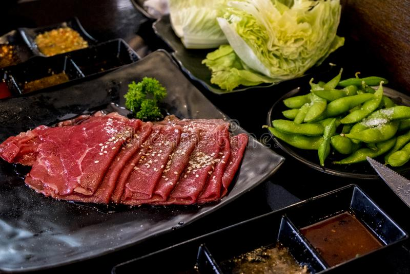 Διάφορες περικοπές του ακατέργαστου κρέατος που πυροβολούνται άνωθεν σε μια σχάρα χυτοσιδήρου στοκ εικόνες