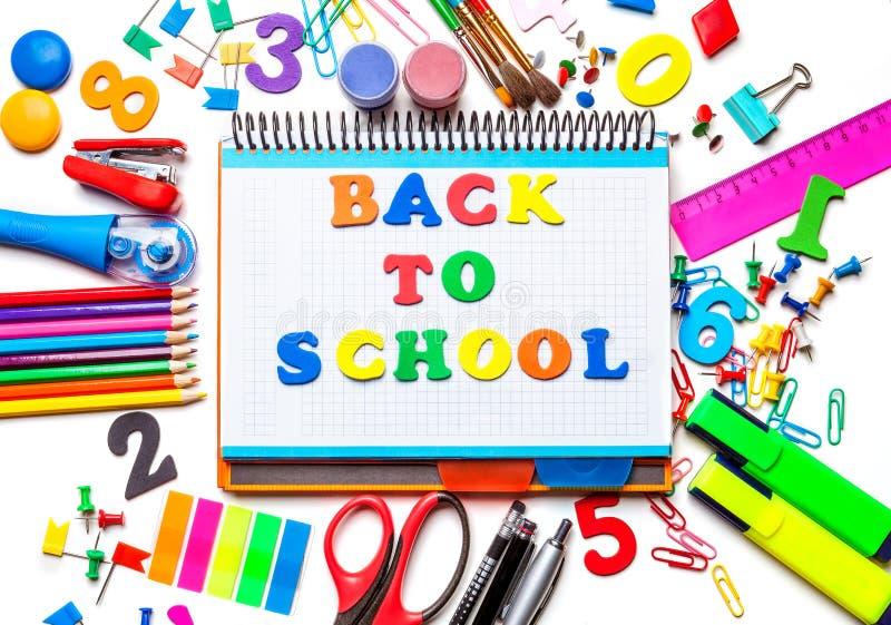 Διάφορες σχολικές προμήθειες που απομονώνονται στο άσπρο υπόβαθρο Σημειωματάριο στο κέντρο της έννοιας πλαισίων πίσω στο σχολείο στοκ εικόνα