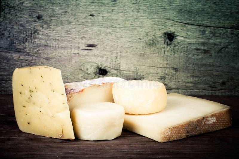Διάφοροι τύποι τυριών σε ένα ξύλινο υπόβαθρο βαμμένος στοκ εικόνα