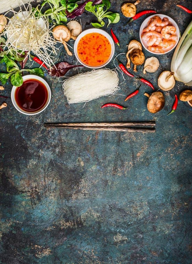 Διάφορος των ασιατικών μαγειρεύοντας μαγειρεύοντας συστατικών και των σαλτσών με chopsticks στο αγροτικό υπόβαθρο, τοπ άποψη, θέσ στοκ φωτογραφία