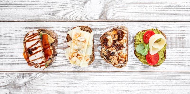 Διάφορος των σάντουιτς προγευμάτων με το τυρί, σαλάμι, ζαμπόν στο ξύλινο υπόβαθρο στοκ φωτογραφία με δικαίωμα ελεύθερης χρήσης