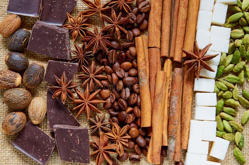 Διάφορο αρωματικό γλυκάνισο αστεριών καρυκευμάτων, κανέλα, μοσχοκάρυδο, κύβοι ζάχαρης, φασόλια καφέ, στενός επάνω σοκολάτας Συστα στοκ φωτογραφία