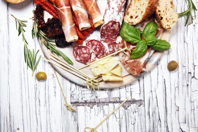 Διάφορο ορεκτικό Antipasto Τέμνων πίνακας με το prosciutto, το σαλάμι, το τυρί, το ψωμί και τις ελιές στο άσπρο ξύλινο υπόβαθρο στοκ εικόνες
