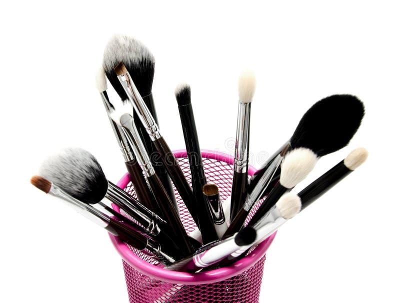 Διάφορο σύνολο επαγγελματικών βουρτσών makeup στον κάτοχο που απομονώνεται στοκ εικόνες