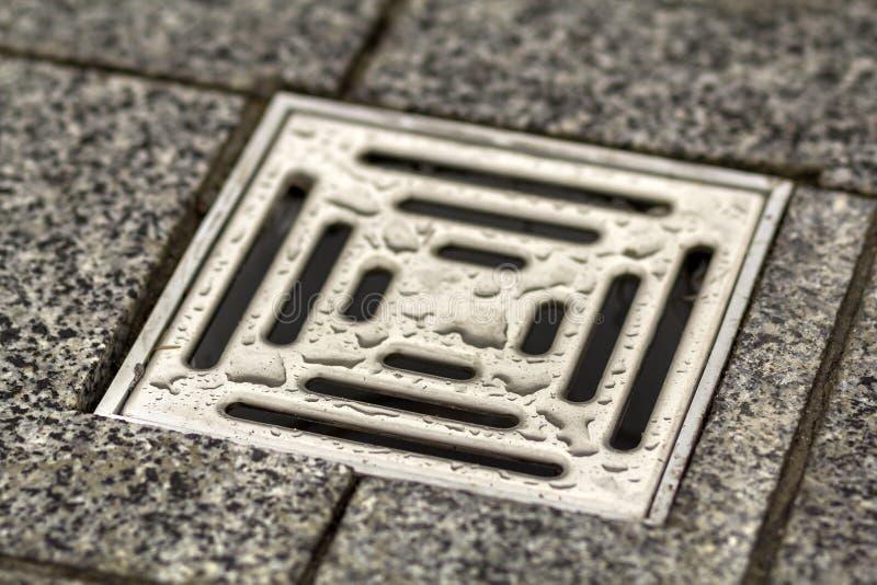 Διέξοδος αγωγών νερού στο κεραμικό κεραμωμένο παλαιό εκλεκτής ποιότητας πάτωμα κουζινών, λουτρών ή υπογείων Γεωμετρικό αφηρημένο  στοκ εικόνες