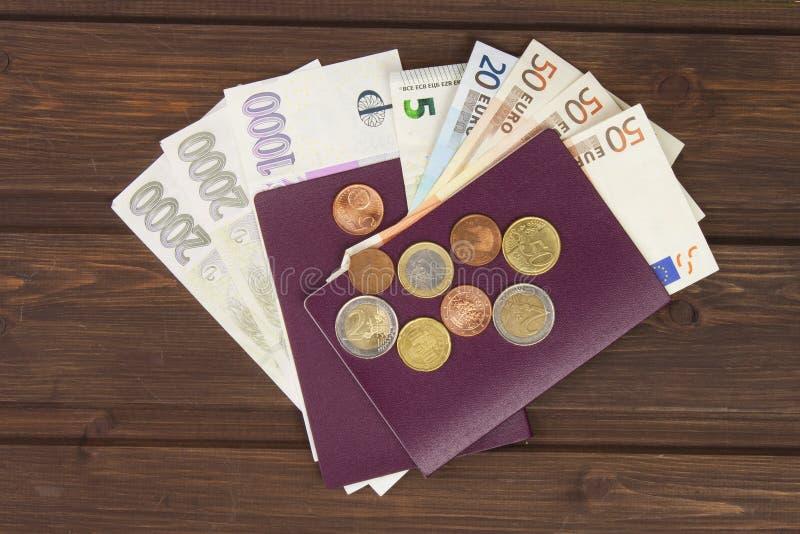 Διαβατήριο και χρήματα στον ξύλινο πίνακα Έγκυρα ΕΥΡΟ- τραπεζογραμμάτια, νομίσματα και τραπεζογραμμάτια τσέχικα Παράνομη μετανάστ στοκ φωτογραφία