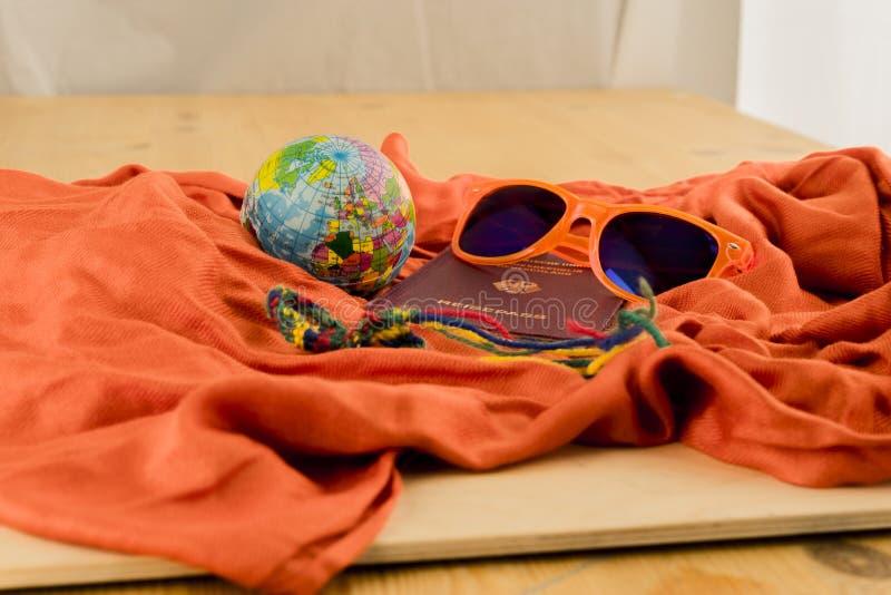Διαβατήριο, σφαίρα και γυαλιά ηλίου στο πορτοκαλί κάλυμμα στοκ εικόνες