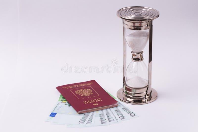 Διαβατήριο της Ρωσικής Ομοσπονδίας με τα ευρο- τραπεζογραμμάτια και της κλεψύδρας σε ένα άσπρο υπόβαθρο στοκ εικόνες
