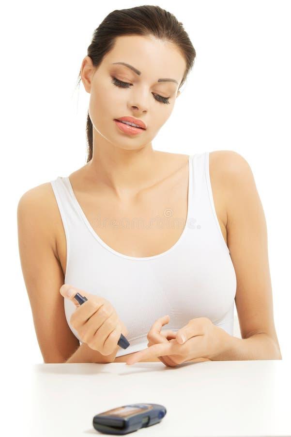 Διαβητική γυναίκα που ελέγχει το επίπεδο ζάχαρής της στοκ φωτογραφία