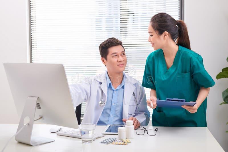 Διαβούλευση δύο ιατρών, που χαμογελά στο γραφείο γραφείων στοκ εικόνα με δικαίωμα ελεύθερης χρήσης