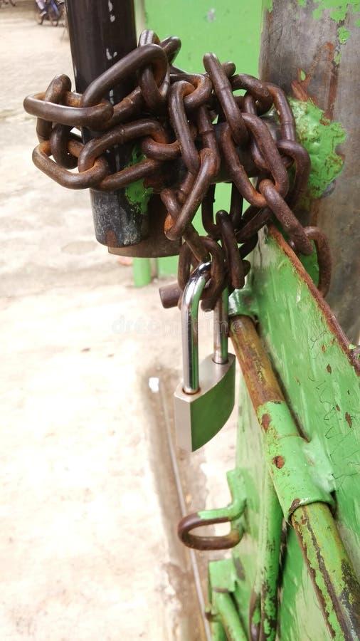 Διαβρωτικά αλυσίδα και λουκέτο στην πράσινη πύλη σιδήρου στοκ εικόνες με δικαίωμα ελεύθερης χρήσης