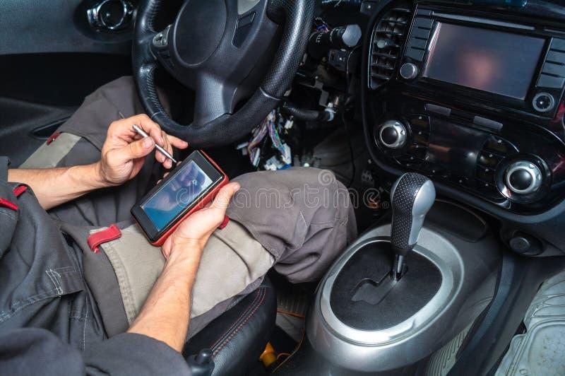 Διαγνωστικά των αποτυχιών αυτοκινήτων: ένας ηλεκτρολόγος στα γκρίζα ενδύματα κάθεται στο εσωτερικό αυτοκινήτων ` s και διαβάζει τ στοκ φωτογραφίες