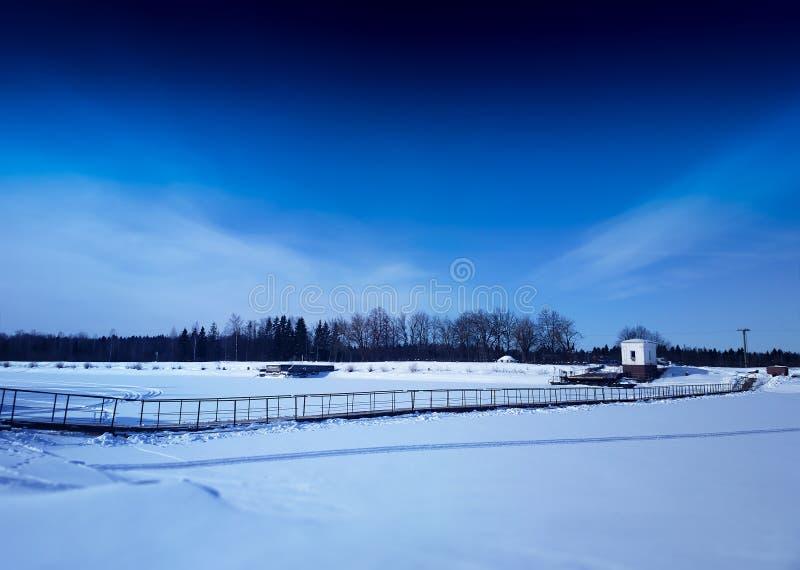Διαγώνια αρθρωμένη γέφυρα πέρα από το παγωμένο υπόβαθρο τοπίων ποταμών στοκ φωτογραφίες