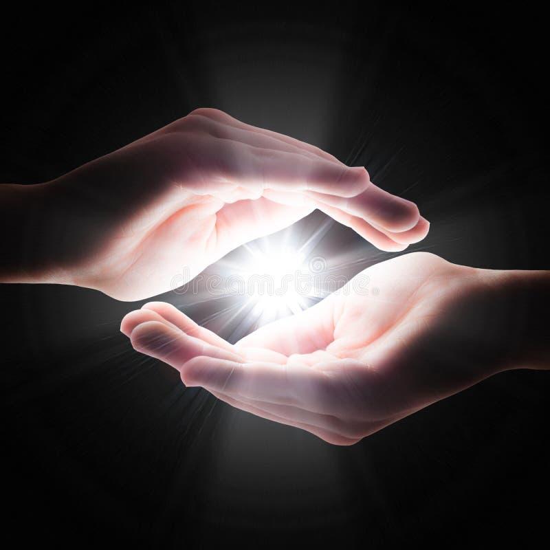 Διαγώνιο φως στο σκοτάδι στα χέρια σας στοκ φωτογραφίες