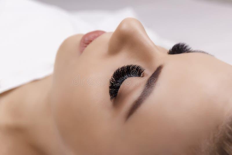 Διαδικασία επέκτασης Eyelash Μάτι γυναικών με τα μακροχρόνια eyelashes Κλείστε επάνω, εκλεκτική εστίαση Hollywood, ρωσικός όγκος στοκ φωτογραφίες