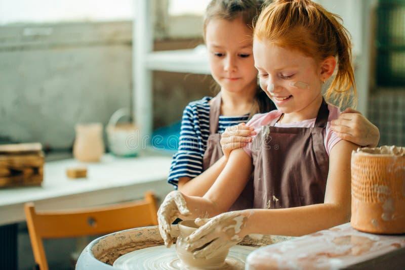 Διαδικασία εργασίας με τη ρόδα αγγειοπλαστών αργίλου Δύο κορίτσια που κάνουν την αγγειοπλαστική στο στούντιο στοκ εικόνες με δικαίωμα ελεύθερης χρήσης