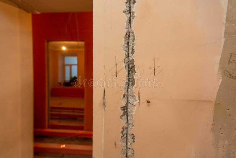 Διαδικασία εργασίας στο αυλάκι ή τοίχος που χαράζει για τα ηλεκτρικά, καλώδια Διαδικτύου και τις ηλεκτρικές εξόδους πρίν επικονιά στοκ εικόνες