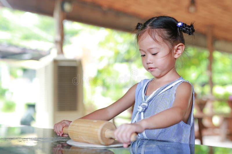 Διαδικασία μικρών κοριτσιών της σπιτικής πίτσας προετοιμασιών Παιδί που χρησιμοποιεί την ξύλινη κυλώντας καρφίτσα στη ζύμη στοκ εικόνες