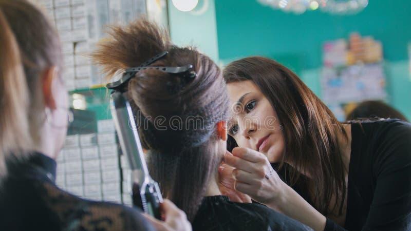 Διαδικασία σύνθεσης στο κατάστημα ομορφιάς για τη νέα μαύρη μαλλιαρή γυναίκα - που κάνει το visage για τα μάτια στοκ φωτογραφία