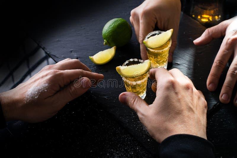 Διαδικασία του χρυσού μεξικάνικου tequila κατανάλωσης με τον ασβέστη και του άλατος στο δ στοκ εικόνα