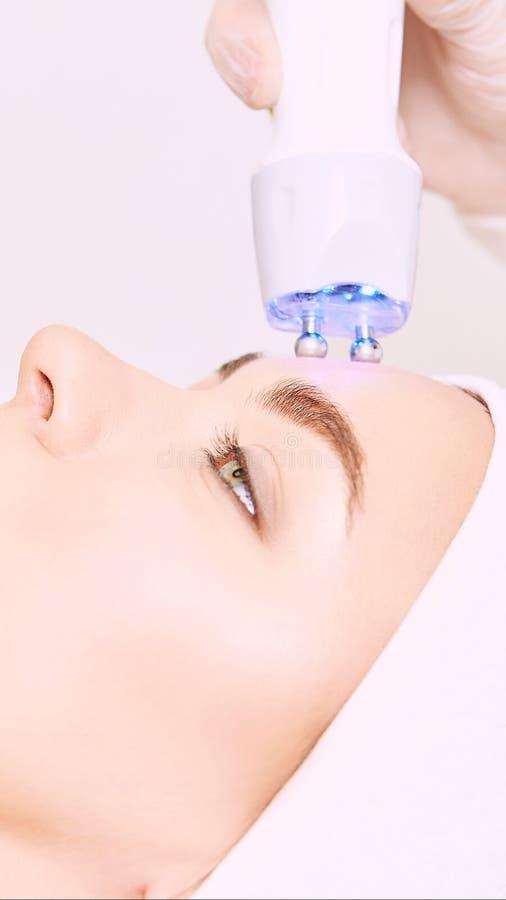 Διαδικασία φωτοκυκλοφορούντων αισθητικών Πρόσωπο κοριτσιού ομορφιάς Συσκευή καλλυντικών Χέρια γιατρού Δύο μπαλάκια Μείωση ρυτίδων στοκ φωτογραφία με δικαίωμα ελεύθερης χρήσης