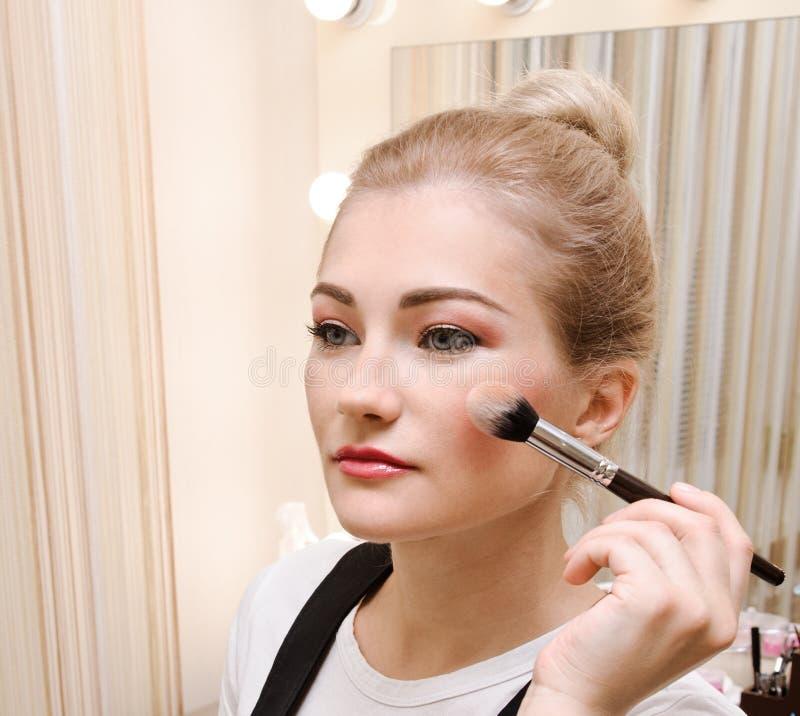 Διαδικασία makeup Όμορφη νέα γυναίκα που εφαρμόζει τον τόνο στο δέρμα στοκ εικόνα