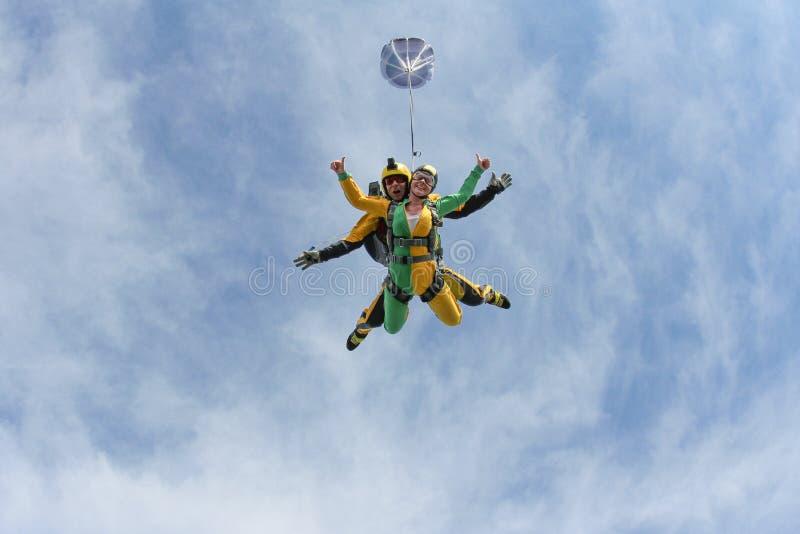 Διαδοχική ελεύθερη πτώση με αλεξίπτωτο Ένα ενεργό κορίτσι πετά στο μπλε ουρανό στοκ εικόνες