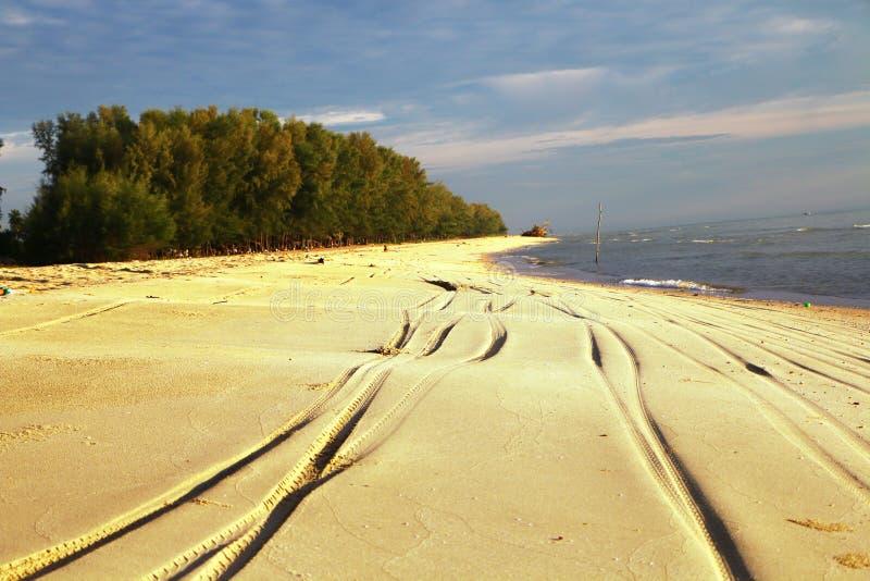Διαδρομές ελαστικών αυτοκινήτου στην άμμο στην παραλία στοκ φωτογραφίες