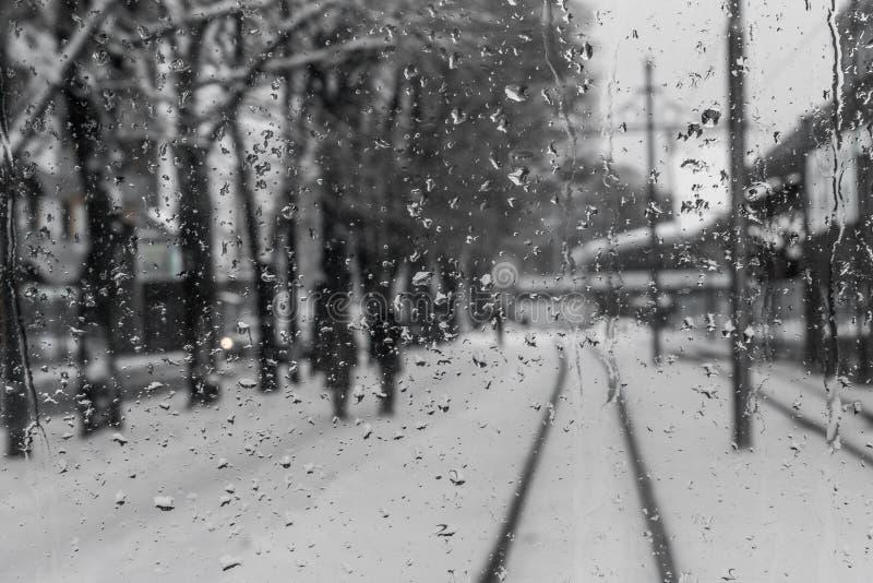 Διαδρομές τραίνων πίσω από ένα μουτζουρωμένο παράθυρο με τις σταγόνες βροχής στοκ φωτογραφία