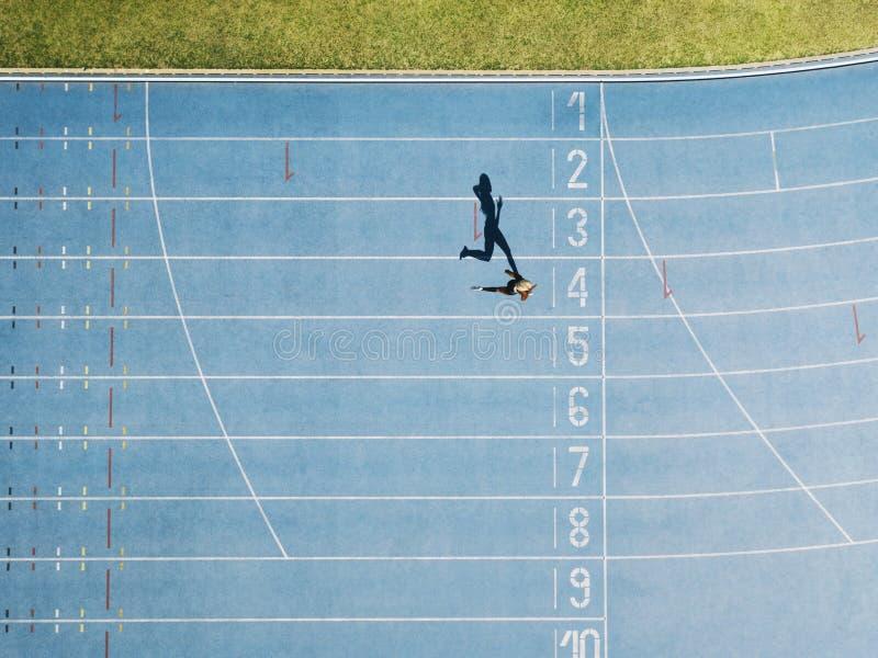 Διαδρομή στίβου με το sprinter στον υπερυψωμένο πυροβολισμό στοκ φωτογραφίες