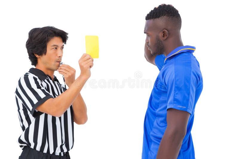 Διαιτητής που παρουσιάζει κίτρινη κάρτα στο ποδοσφαιριστή στοκ εικόνα με δικαίωμα ελεύθερης χρήσης
