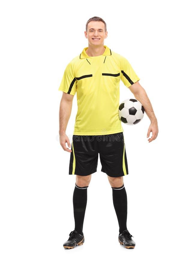 Διαιτητής ποδοσφαίρου σε ένα κίτρινο Τζέρσεϋ που κρατά μια σφαίρα στοκ εικόνα
